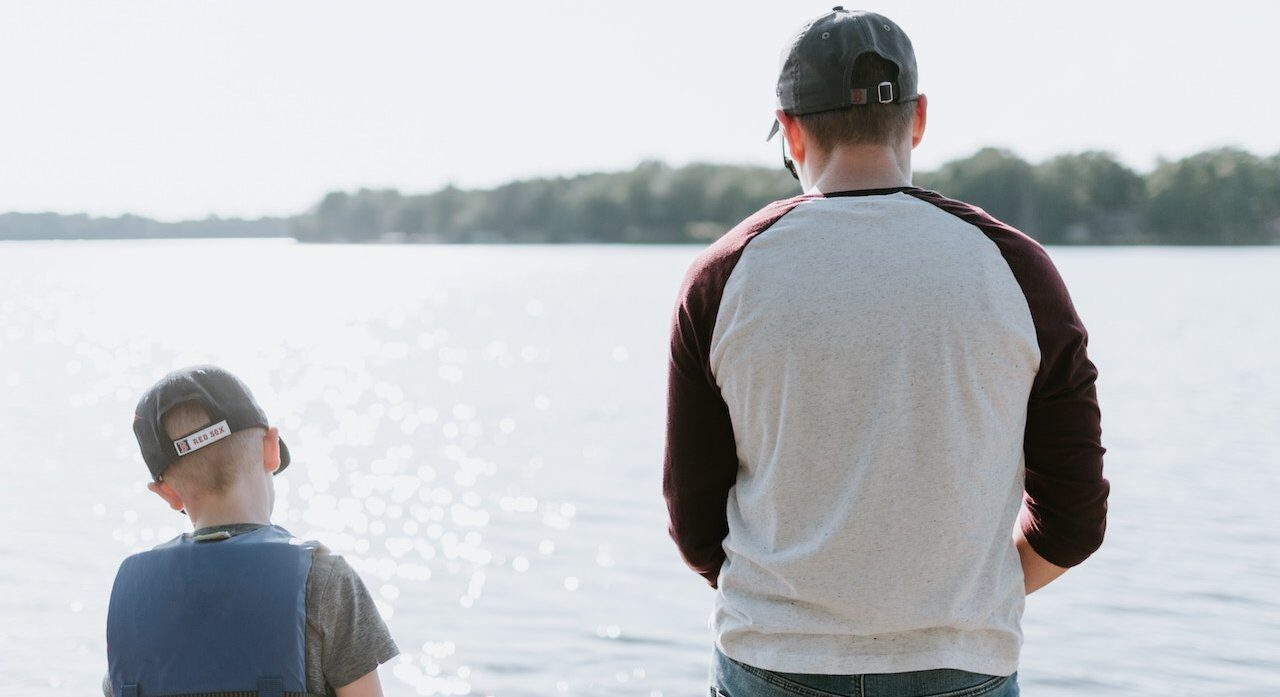 father and son standing at the edge of a lake fishing