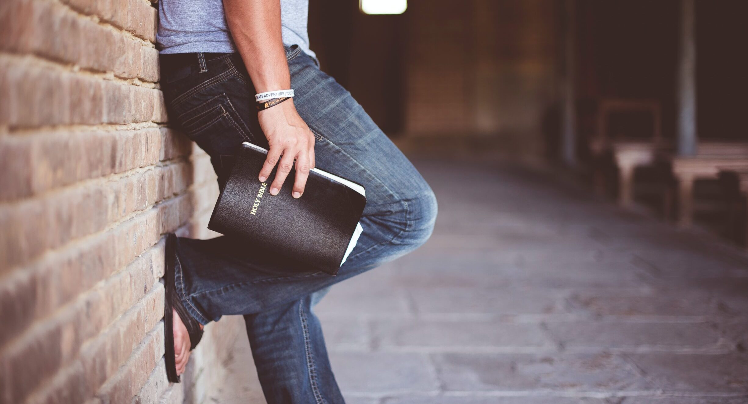 Man leaning against brick wall while holding a Bible